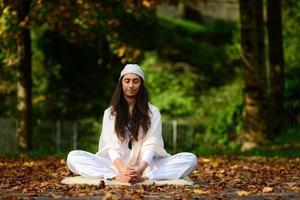 donna in bianco nel parco autunnale mentre fa yoga foto