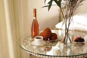 tavolo in vetro con una tazza di caffè, croissant dolci foto