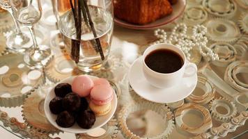 tavolo in vetro con una tazza di caffè, amaretti dolci. foto