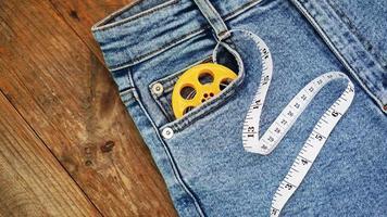blue jeans e un metro a nastro. concetto di denim dimagrante o cucito foto