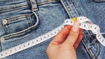 una mano femminile tiene un metro a nastro su uno sfondo di jeans foto