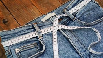 metro a nastro e jeans su uno sfondo di legno foto