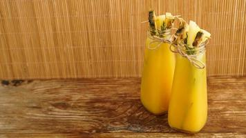 succo d'ananas in una bottiglietta. fette di ananas decorano la bevanda foto