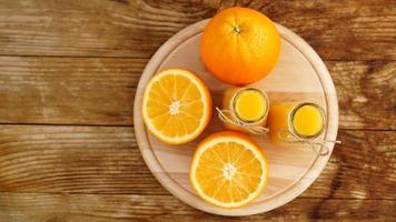 succo d'arancia fresco sul tavolo di legno su una tavola di legno foto