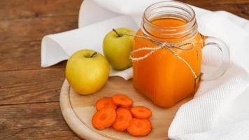 succo di mela e carota in vetro, verdure fresche e frutta su legno foto