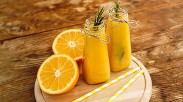 succo d'arancia in bottiglie di vetro. il succo è decorato foto