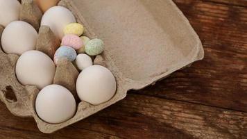 uova di gallina in un vassoio di cartone e decorazioni pasquali su un legno foto