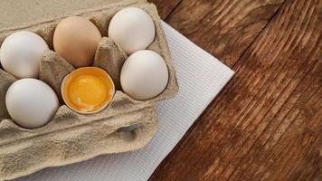 cartone di uova bianche e metà dell'uovo incrinato con vista dall'alto del tuorlo foto