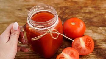 la mano femminile tiene un bicchiere di succo di pomodoro sul tavolo di legno foto