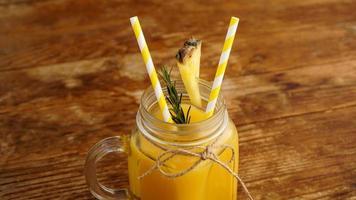 succo d'ananas in un barattolo di vetro. fette di ananas decorano la bevanda foto