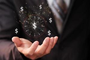 uomo d'affari che tiene il segno dell'orologio e il tempo degli affari è denaro foto