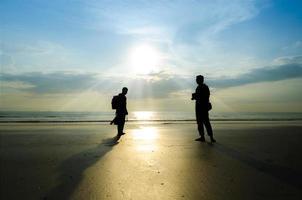 silhouette di giovani fotografi sulla spiaggia foto