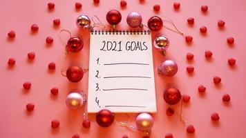 lista degli obiettivi per il 2021. sfondo rosa con palle di natale foto