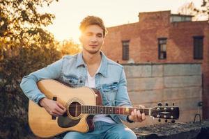 giovane che suona la chitarra in città sullo sfondo dei raggi del sole foto