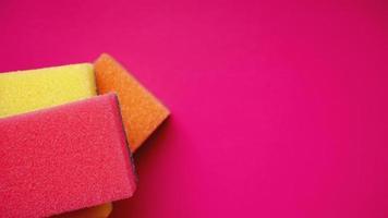 concetto di pulizia della casa. spugne colorate su sfondo rosa foto