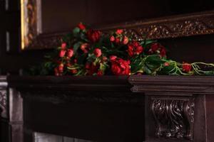 una composizione di fiori finti su una mensola del camino foto