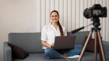 blogger femminile sorridente registra un nuovo video foto