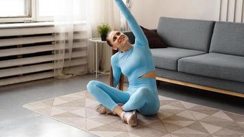 giovane determinata donna magra fiduciosa che fa esercizi a casa foto