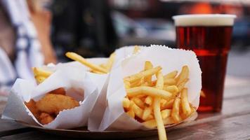 birra scura e patatine fritte su un tavolo di legno. punto ristoro. cibo da asporto foto