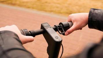 primo piano della mano maschile che preme il pulsante di velocità su scooter elettrico foto
