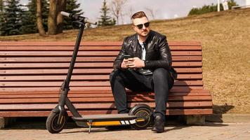 il giovane si siede su una panchina in un giorno di primavera foto