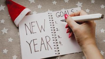 il taccuino è con il testo degli obiettivi del nuovo anno con la mano foto