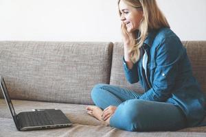 bionda sorridente che si rilassa sul divano con il suo laptop foto