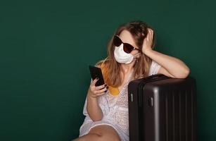 ragazza turista in una maschera medica si siede con i bagagli su uno sfondo verde foto