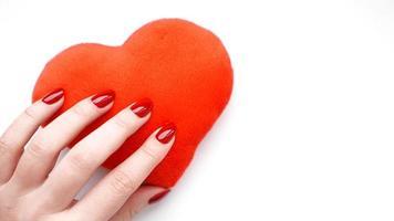 mano femminile con cuore rosso isolato su bianco foto