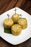 Pannocchie di mais dolce organiche tapas vegane snack su tavola di legno sfondo foto
