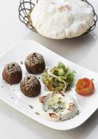 Falafel biologico e hummus antipasto snack mezze piatto sul tavolo bianco foto