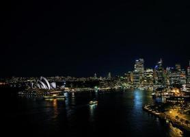 Sydney City Harbour con l'orizzonte del punto di riferimento del teatro dell'opera di notte in australia foto