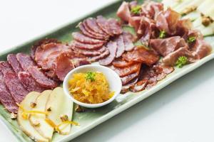 prosciutto serrano spagnolo chorizo salsiccia carni affumicate formaggio tapas condivisione piatto con pane foto