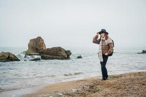 donna in cappello e con zaino sulla spiaggia su uno sfondo di mare foto