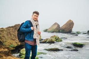 l'uomo viaggiatore con uno zaino si erge su una roccia contro un bellissimo mare foto