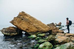 Turista in cappello con zaino sulle rocce su uno sfondo di mare foto