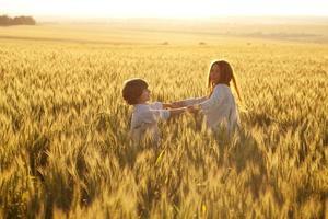 madre e figlio felici stanno correndo attraverso un campo di grano foto