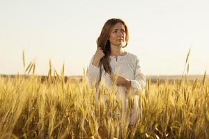 giovane donna sta in mezzo a un campo di grano foto