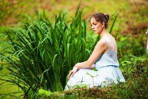 la giovane donna in un vestito blu si siede sull'erba foto