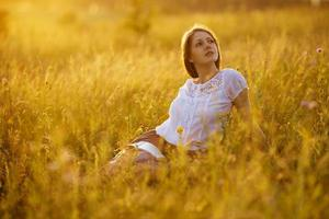 donna felice con un libro di fiori di campo foto