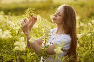 ragazza felice tra gli alti fiori di campo foto