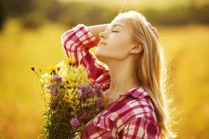 ragazza felice con un mazzo di fiori selvatici foto