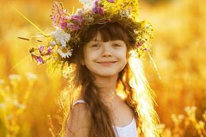 felice ragazza carina che indossa una ghirlanda di fiori foto