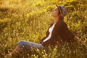ragazza si siede tra i fiori di campo foto