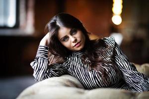 bella ragazza dai capelli scuri si siede sul divano foto
