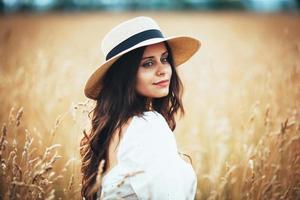 bella donna con cappello di paglia tra l'erba del campo foto