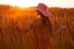 donna felice in un cappello dell'erba del prato foto