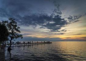 I turisti visualizzano il tramonto dal molo di kep città sulla costa della Cambogia foto