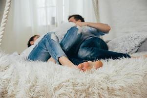una giovane coppia in jeans su un letto impiccato foto