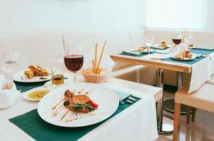 allestimento da pranzo con bicchieri da vino e acqua, posate in tovaglioli verdi, cibo servito su piatti bianchi, organizzato dal servizio di catering in un moderno ristorante luminoso, caffetteria. cucina italiana europea foto